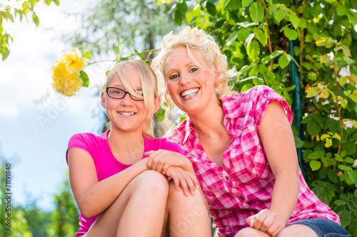 canvas print picture Familie sitzt im Garten und genießt die Sonne