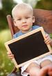 Little boy with blackboard in nature