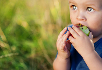 Cute boy eating apple