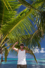 Man Standing Beneath Palm Tree on Tropical Beach