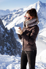 Young beautiful woman with smartphone on the top of the mountain