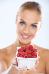 Woman showing fresh and nutritious raspberries