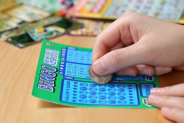 Woman scratching lottery ticket called Bingo.