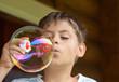 Boy blowing soap bubble