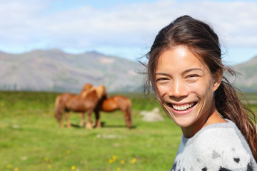 Woman on Iceland smiling with Icelandic horses