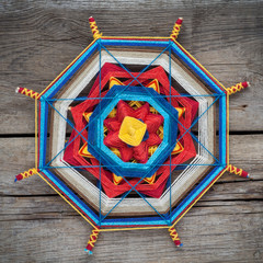 Knitted mandala on wooden plank