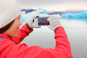 Woman taking smartphone photo, Jokulsarlon Iceland