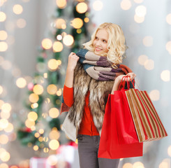 smiling young woman with red shopping bags