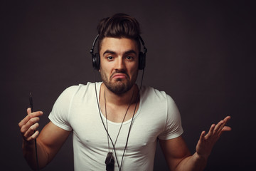 Handsome DJ posing in studio on dark background with headphones