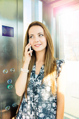 Beautiful woman at mobile phone in an elevator
