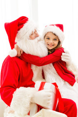 smiling girl with santa claus and gift at home