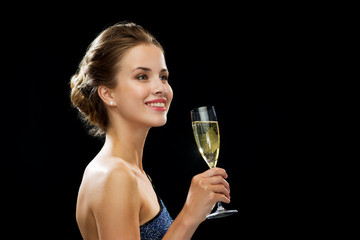 smiling woman holding glass of sparkling wine