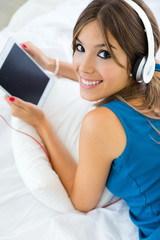 Beautiful girl listening to music with tablet on sofa at home.