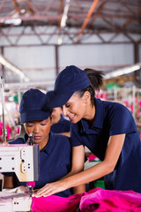 young woman teaching new machinist to sew