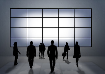 Some people (silhouettes) looking to a very big tv panel