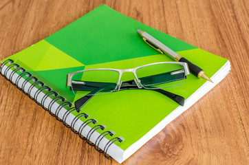 Green diary  with black glassess and gold pen on wood table