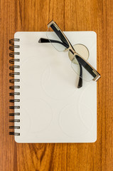 White diary and black glasses on wood table