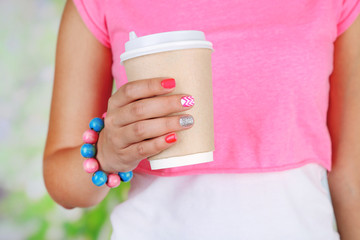 Woman with stylish colorful nails holding mug, close-up,