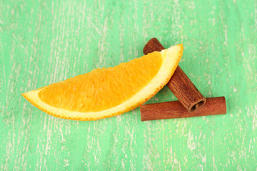 Piece of orange and seasoning on green background