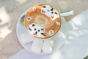 Cup of coffee with cute drawing on table, close up © Africa Studio