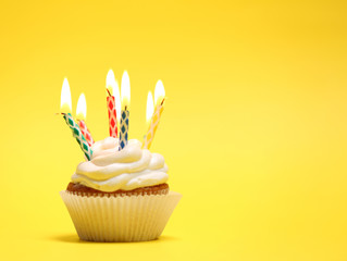 Delicious birthday cupcake on table on yellow background