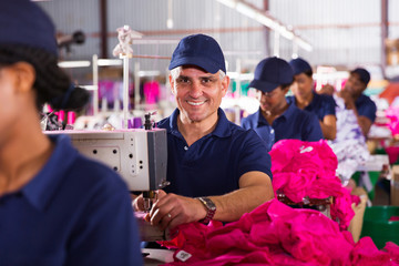 middle aged male textile worker sewing in factory