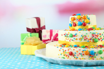 Beautiful tasty birthday cake and gifts on light background
