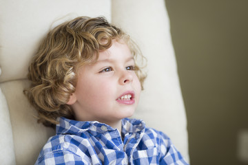 Cute Blonde Boy Daydreaming and Sitting in Chair
