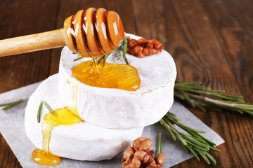 Camembert cheese, honey and nuts on napkin on wooden background