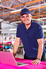 middle aged textile factory worker using computer