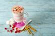 Leinwandbild Motiv Cranberry milk dessert in glass, on color wooden background