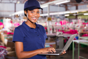 african factory supervisor using laptop