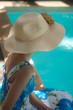 jeune fille au chapeau au bord d'une piscine