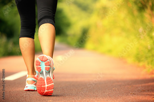 young fitness woman legs walking on forest trail  - 71206480