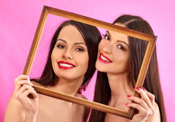 Lesbian women holding  art frame.