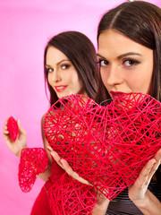 Lesbian women holding heart symbol.