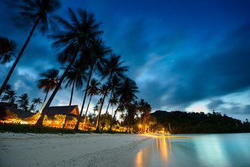 Bungalows, palms and beach at sunset in thailand paradise