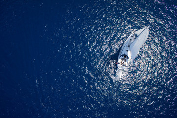 Yacht sailing in open sea at windy day. Drone view