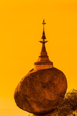 Kyaikhtiyo pagoda or Golden rock with sunset sky in Myanmar