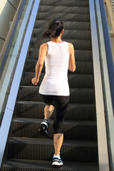 Runner athlete running on escalator stairs.