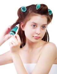 Young beautiful girl having hair curlers on her head isolated