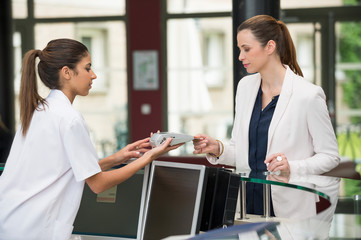 Female doctor making payment with credit card at hospital reception desk