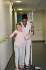Female nurse helping to a girl patient to walk in hospital corridor