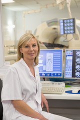 Female doctor smiling in medical MRI scan monitor room