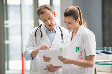 Two doctors discussing medical report in hospital