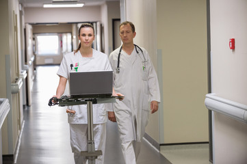 Doctor and female nurse carrying a laptop in a hospital corridor