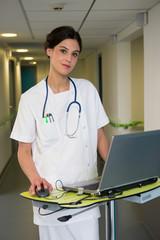 Female nurse using laptop in hospital corridor