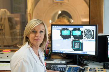 Female doctor examining brain MRI scan on computer