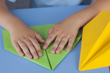 Child making a paper plane