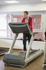 Man running on a treadmill in a gym